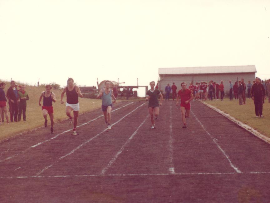 [Fünf Sprinter sind auf der Laufbahn zu sehen. Im Hintergrund und am linken Rand schauen ihnen weitere Sportler zu. Im Hintergrund ist eine weiße eingezäunte Baracke zu sehen.]