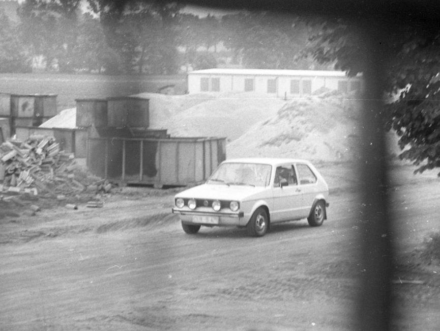 [Das schwarzweiße Lichtbild zeigt einen hellen VW Golf I, wie er auf einem Sandweg vermutlich auf einer Baustelle entlang fährt. Im Hintergrund ist links eine Anhäufung von Dachziegeln zu sehen, daneben wurden mehrere leere Container übereinander gestapelt. Dahinter befinden sich mehrere Sandberge vor einem Flachbau.]