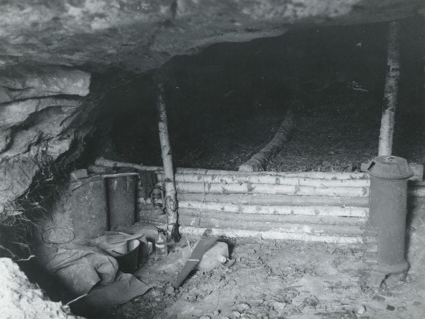 Das Bild, eine Schwarzweißfotografie, zeigt das Innere der Boofe. Im Vordergrund sind auf der linken Seite Töpfe und anderes Kochgeschirr zu sehen und rechts ein weiteres längliches Gerät aus Metall. Hinter einer niedrigen Absperrung aus Birkenästen geht es tiefer in den Fels hinein, wo der Boden mit Laub ausgelegt ist.