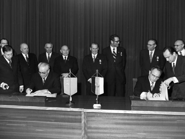 [Das schwarz-weiße Lichtbild zeigt Erich Mielke rechts von Juri Andropow, dem Vorsitzenden des KGB, wie sie hinter einem langen Tisch sitzen und feierlich Schriftstücke unterzeichnen. Links neben Andropow und rechts neben Mielke stehen die jeweiligen Vertrauten, die die zu unterzeichnenden Unterlagen reichen. Am vorderen Tischende stehen zwischen ihnen Wimpel der Flaggen des vertretenen Landes. Vor einem Vorhang stehen im Hintergrund zehn männliche Personen, jeweils fünf der unterzeichnenden Vertragspartei. Alle beteiligten tragen Anzüge, die Vertreter des MfS jeweils mit einem Orden auf der rechten Seite der Brust.]