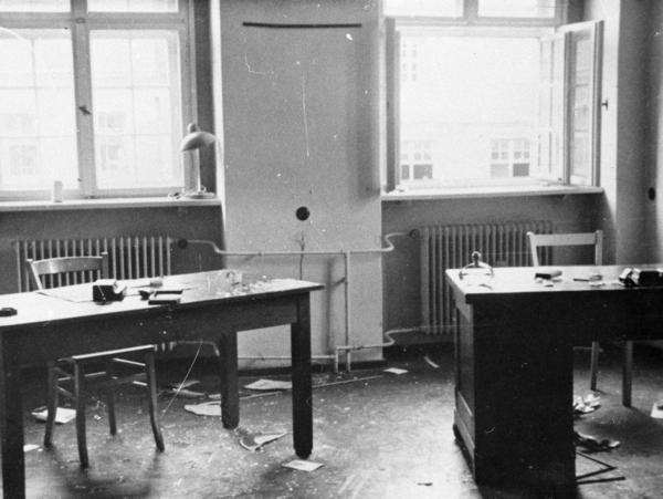 Ein verwüstetes Büro in der Kreisdienststelle der Staatssicherheit in Niesky. Ein Fenster im oberen rechten Teil des Bildes ist weit offen, auf den zwei Schreibtischen und auf dem Boden liegen einige Gegenstände und Papier.