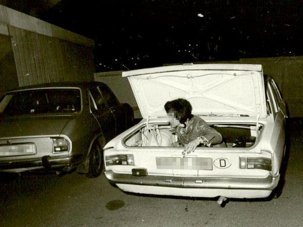 [Es handelt sich um den Ausschnitt einer Fotodokumentation. Das schwarz-weiße Lichtbild zeigt zwei Autos in Heckansicht, vermutlich vor Garagentoren auf einem Parkplatz. Während das silberne Auto auf der linken Seite verschlossen ist, ist der Kofferraum des weißen Wagen im Bildmittelpunkt geöffnet. In diesem setzt sich gerade eine dunkelhaarige Frau auf, sie ist nur bis zur Taille sichtbar.]