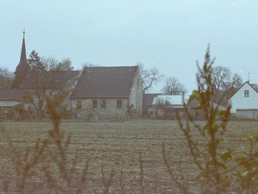 [Zwischen kahlen Zweigen hindurch wurde ein kleiner Landhof fotografiert. davor erstreckt sich ein brachliegeder Acker, im Hintergrund ist ein Kirchturm zu sehen.]