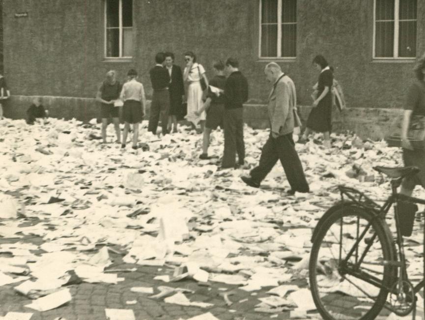 Einige Personen stehen auf einer Straße. Die Straße ist übersät von Papier aus Akten.