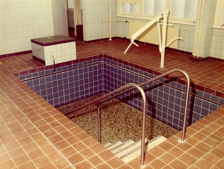 Das Bild zeigt ein kleines Tauch- bzw. Schwimmbecken im Stasi-Krankenhaus in Berlin-Buch. Das Becken befindet sich inmitten eines gefliesten Bereichs. Neben dem Becken befindet sich ein fest installierter Greifarm, bestimmt dazu einen Menschen über Wasser zu halten, um ihm beim Schwimmen zu unterstützen.