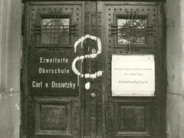 Eingangstür der Carl-von-Ossietzky-Schule mit aufgemaltem Fragezeichen.