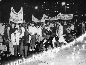 [Eine Reihe brennender Kerzen wird an einem Treppenabsatz aufgestellt, einige Menschen sind dabei  auf schwarzweißem Foto abgelichtet worden. Dahinter ziehen Demonstranten mit Transparenten vorbei.]