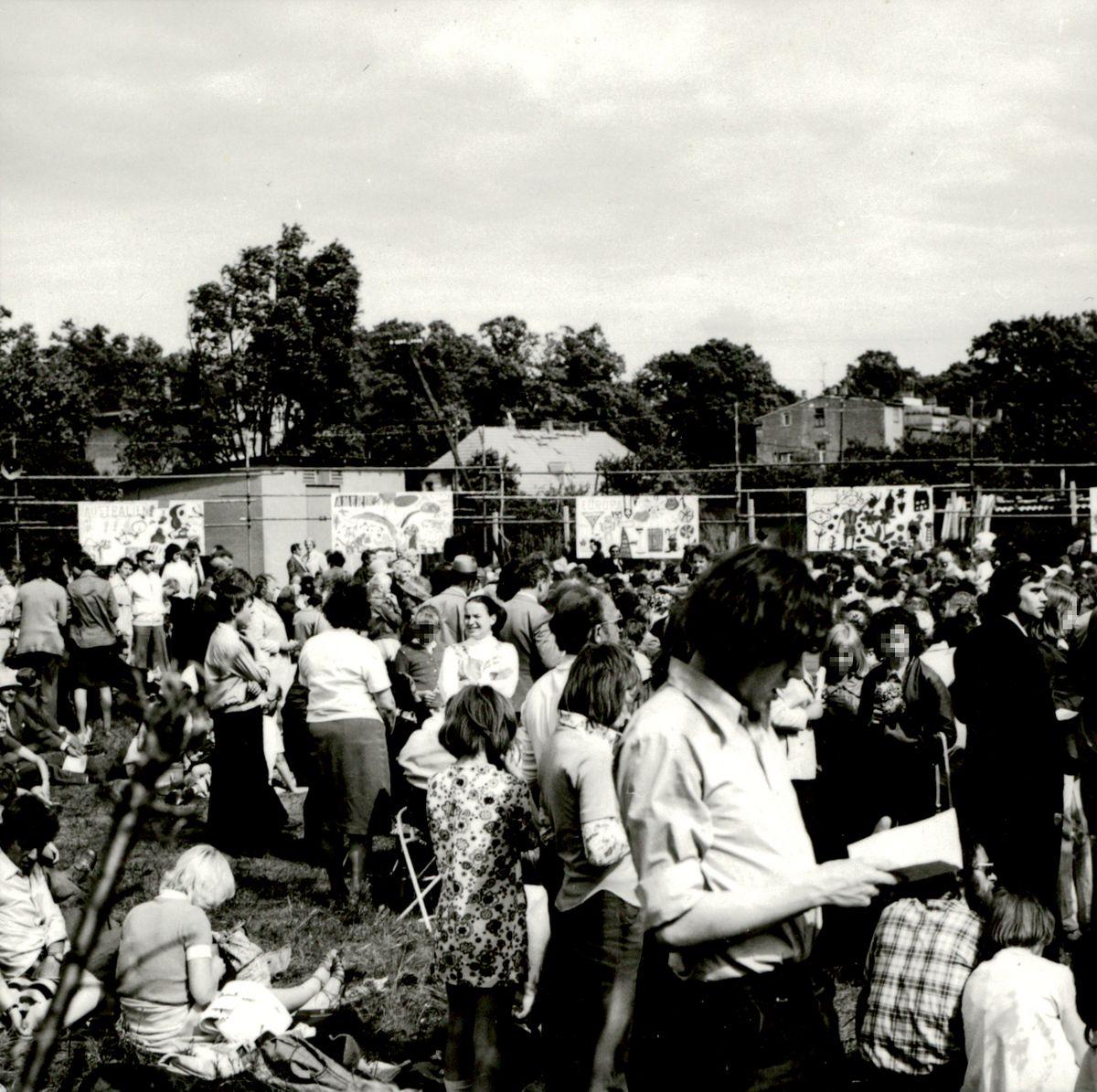 [Das schwarz-weiße Lichtbild zeigt eine Ansammlung von Menschen auf einem freien Platz. Überwiegend stehen die Personen allen Alters auf der Rasenfläche. Im Hintergrund sind kindlich bemalte Transparente an Zäunen angebracht.]