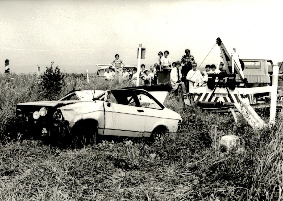 Das Schwarz-Weiß-Bild zeigt den stark beschädigten Unfallwagen, der mit einer Seilwinde abgeschleppt wird.. Im Hintergrund beobachten mehrere Personen, darunter auch Kinder, das Geschehen.