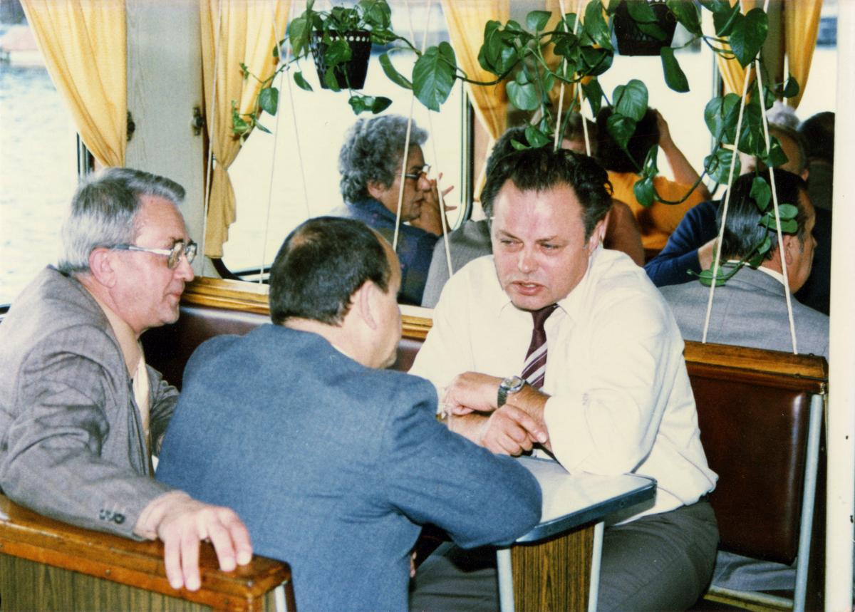 Das farbige Lichtbild zeigt im Vordergrund drei Herren, die sich an einem Tisch gegenüber sitzen und in ein Gespräch vertieft sind. Im Hintergrund sitzen weitere durchmischte Personengruppen an Tischen zusammen, es handelt sich sich um eine Bootsfahrt.