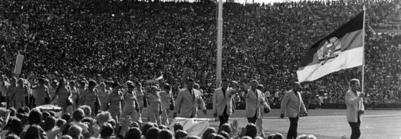 Die DDR-Olympiamannschaft marschiert bei der Eröffnungszeremonie der Olympischen Spiele 1972 im Olympiastadion München ein. Ein Flaggenschwenker hält vorneweg gehend die DDR-Flagge.
