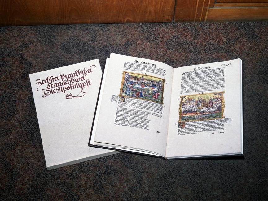 Das Bild zeigt zwei Bücher, eins geschlossen, eins geöffnet. Auf dem Umschlag des geschlossenen Buches steht in verzierter, goldener Schrift 'Zerbster Prunkbibel / 'Granachbibel' / Die Apokalypse'.