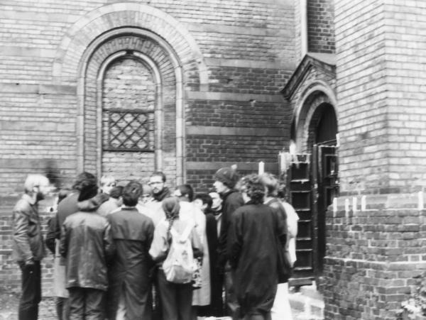 Ein Gruppe von Teilnehmerinnen und Teilnehmer einer Mahnwache steht vor der Zionskirche. Sie protestieren gegen Festnahmen in der Umweltbibliothek Ende November 1987.