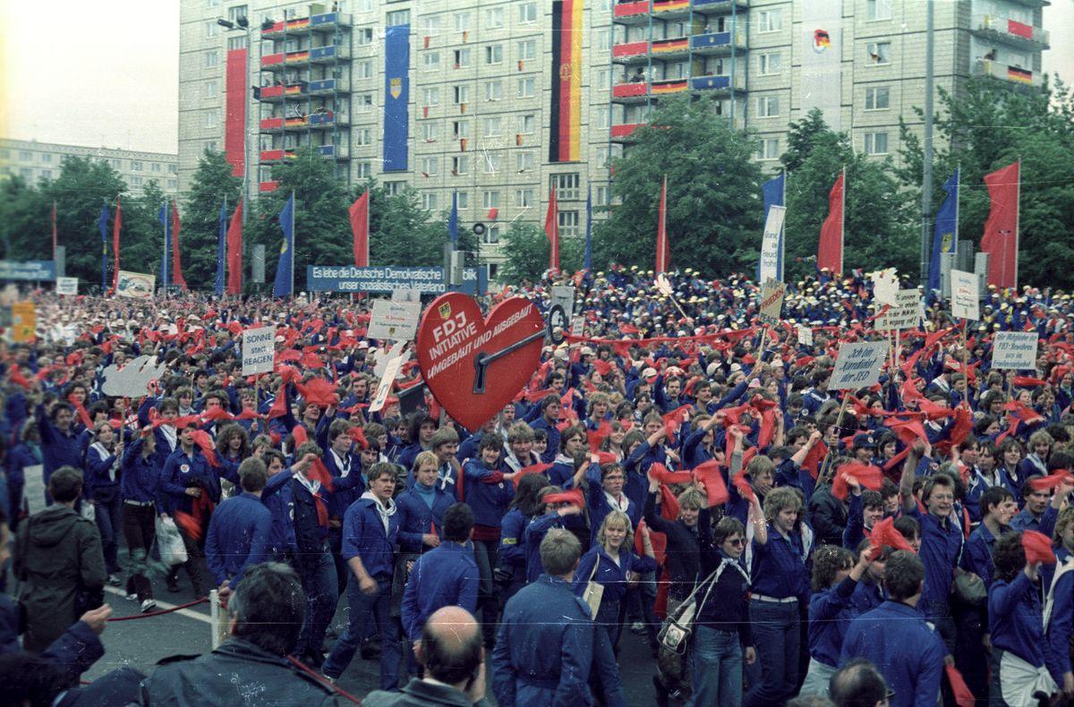 Junge Menschen in blauen FDJ-Hemden. Viele von ihnen winken mit roten Tüchern, einige tragen Schilder.