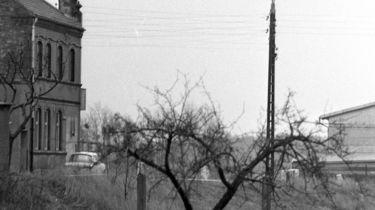 [Das Schwarzweiß-Positiv zeigt die Ecke eines merkstöckigen Backsteinhauses. Davor ist ein heller Trabant zu sehen. Markant ist rechts davon ein Strommast, der gleichzeitig als dreistrahlige Straßenlaterne dient. Im hintergrund ist ein Teil der Stirnseite eines langen Flachbaus zu sehen.]