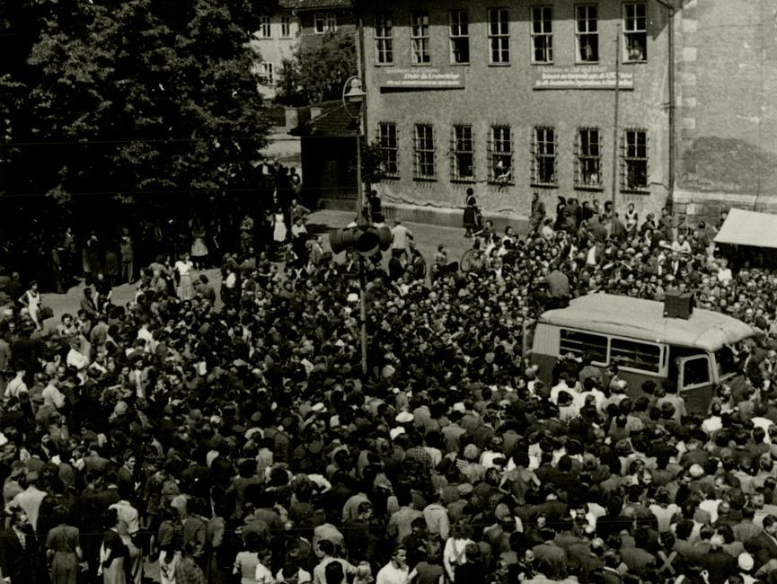 Der Marktplatz der thüringischen Stadt Sömmerda am 17. Juni 1953. Auf dem Platz hat sich eine große Menge Menschen eingefunden. Inmitten der Menge ist ein Mast mit Lautsprechern zu sehen, daneben ein Kleinbus mit Lautsprecheraufbauten. Es handelt sich um Lautsprecherausrüstung des nahen VEB Mechanik Büromaschinenwerk Rheinmetall. Viele der Menschen sind wahrscheinlich Arbeiter des Werks, das am 17. Juni bestreikt wurde.  Auf der Rückseite des Fotos ist handschriftlich vermerkt: 'Sömmerda am 17.6.53 – Marktplatz mit Lautsprecherwagen des VEB Rheinmetall vorm Rathaus. Kundgebung der Arbeiter der Rheinmetall.'