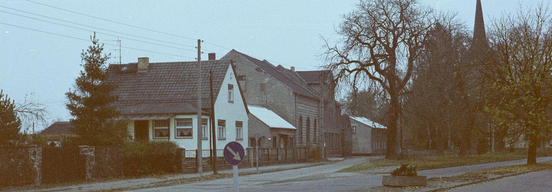 [Der Verlauf einer asphaltierten Straße wird vom Gelände mit einer Dorfkirche geteilt, die umgebenden Bäume sind kahl. Auf der linken Seite ist ein Häuserzug zu sehen. Es handelt sich um ein Farbnegativ.]