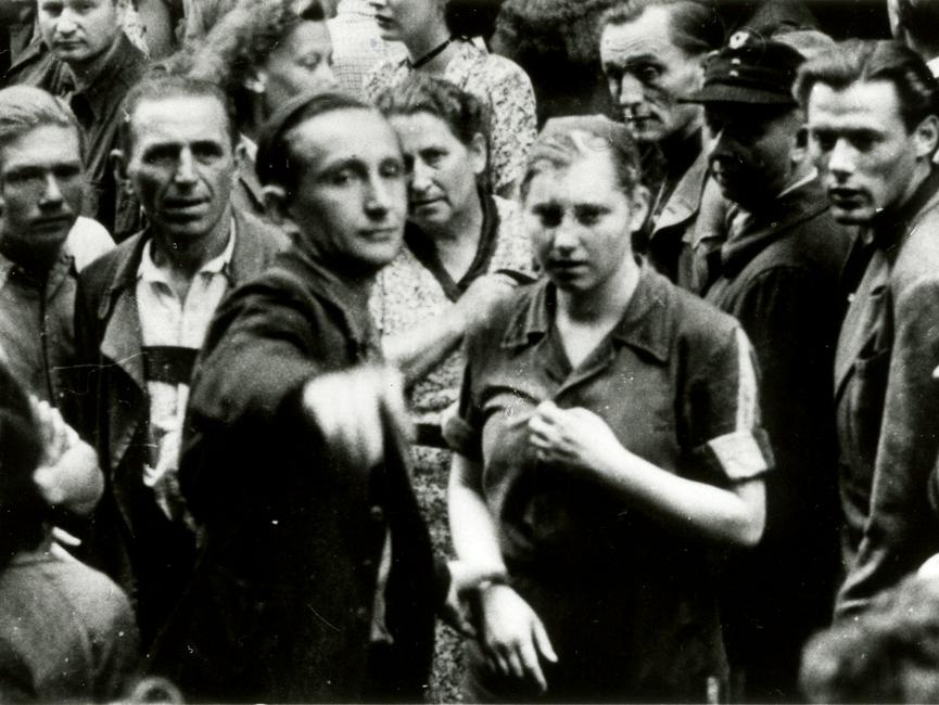 ie Schwarz-Weiß-Aufnahme zeigt eine Gruppe von Menschen. In der Mitte stehen ein Mann und eine Frau. Der Mann zeigt in Richtung des Betrachters oder der Betrachterin des Bildes.