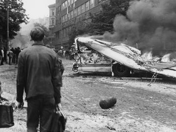 Der Betrachter des Schwarz-Weiß-Bildes sieht einen brennenden Bus. Das Dach des Busses ist in sich zusammengefallen. Teile der Verwüstung liegen auf der Straße. Vorne links im Bild stehen zwei Männer mit Aktentaschen, die das Geschehen beobachten. Im Hintergrund, entlang der Straße sind Menschen zu erkennen.