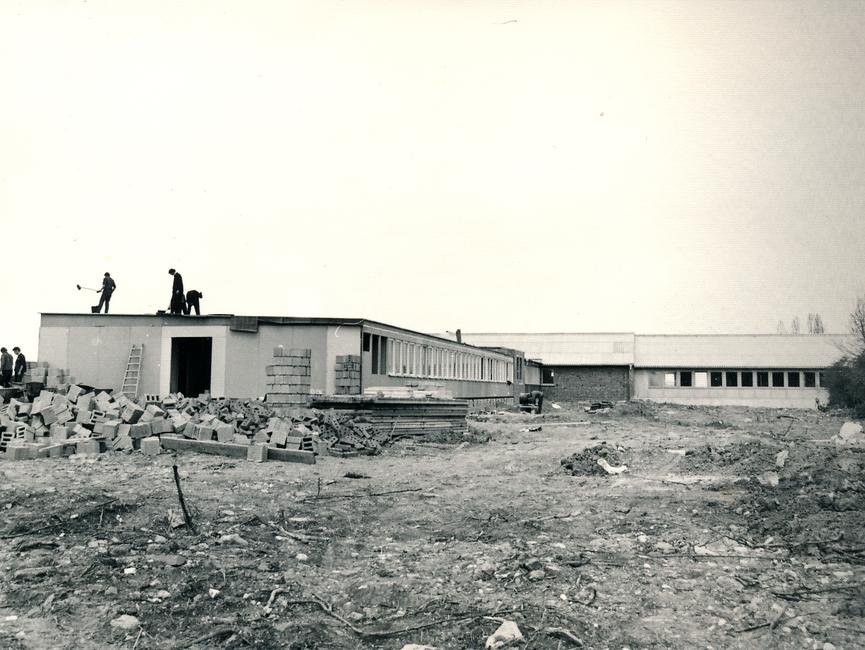 [Zu sehen ist die Stirnseite der Baracke. Es sind drei Männer auf dem Dach und auf der linken SEite wird eine Wand hochgezogen. Daneben liegen Mauersteine aufgeschüttet. Es handelt sich um ein schwarz-weiß Lichtbild.]