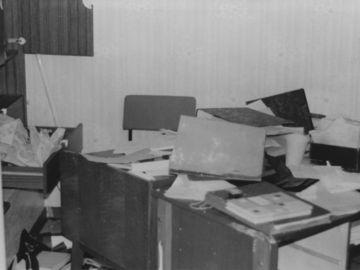 Das Schwarz-Weiß-Bild zeigt ein verwüstetes Büro. Auf dem Schreibtisch und auf dem Boden liegen Akten, ein Karteikasten und Papiere. Schubladen und Türen von einem Schrank sind geöffnet.