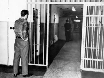 Ein Häftling wird gerade von einem Wärter in seine Zelle gelassen. Ein weiterer Wärter beobachtet das Geschehen.