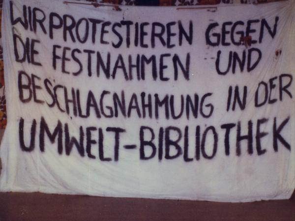 """Beschlagnahmtes Transparent, das Demonstranten am Morgen des 27. November 1987 an den Turm der Zionskirche in Berlin gehängt hatten. Die Aufschrift lautet: """"Wir protestieren gegen die Festnahmen und die Beschlagnahmung in der Umweltbibliothek""""."""