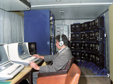 [Das farbige Lichtbild zeigt einen Mann in Uniform im Profil, wie er mit Kopfhörern auf einen schwarzen Computermonitor blickt. Er sitzt in einem Bürosessel am Schreibtisch, neben dem Tischcomputer steht ein Tonbandgerät. Direkt daneben, im Bildvordergrund, ist ein identisch aufgebauter Arbeitsplatz. Im Hintergrund stehen vier Metallständer, bestückt mit jeweils vier Tonbandgeräten. Daneben steht ein Turm mit 14 Kasettenrekordern.]
