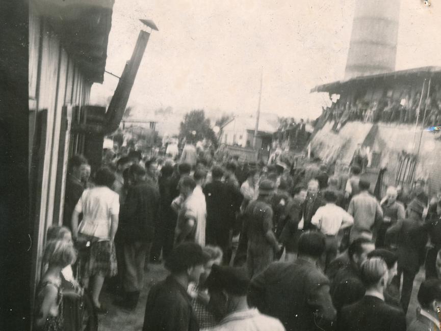Dieses Foto zeigt Demonstranten, welche sich auf dem Bahngelände Belzig befinden. Im Hintergrund der Aufnahme steht ein großer Backsteinschornstein.