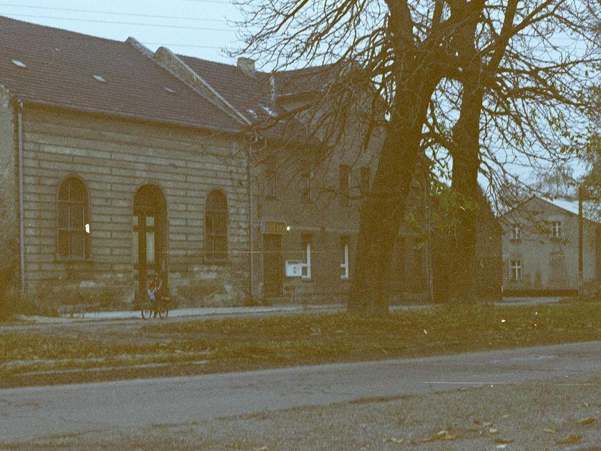 [Zu sehen sind im Bildzentrum des Farbnegativs zwei aneinander gebaute, doppelstöckige Häuser mit Spitzdach. Das linke Haus hat zur Straßenseite mittig eine Rundbogen Eingangstür, die von zwei hohen Rundbogenfenstern eingefasst umrahmt ist. Über dem Eingang der rechten Seite hängt ein rötliches Schild, die Aufschrift ist nicht zu erkennen. Auf der rechten Seite dieser Tür hängt ein weißer Schaukasten.]