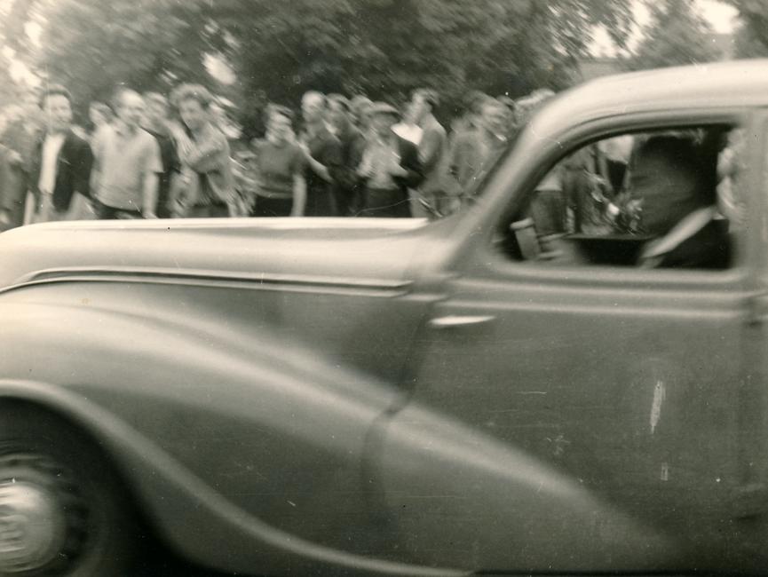 Es handelt sich hierbei um eine verwackelte Aufnahme eines fahrenden Autos auf der auch der Fahrer zu sehen ist. Im Hintergrund sind weitere Demonstranten zu sehen.