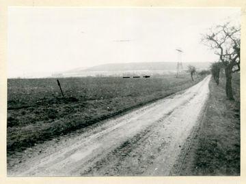 BStU, MfS, HA VII, Nr. 1626, Bl. 11   [Ein aufgeklebtes schwarzweißes Fotopositiv, das im Zentrum eine unbefestigte Straße zeigt. An den Straßenrändern stehen vereinzelte kahle Bäume. Links davon ein brach liegendes Gelände. Ein eingezeichneter Pfeil deutet auf ein winziges Gebäude an der Horizontlinie, auf der auch ein gestrichelter Pfeil nach rechts deutend abgebildet ist. Im Bildhintergrund und wie im Nebel wirkend sind bergige Landschaftserhebungen zu sehen.]  [Stempel: 2] Auf dem Foto ist die Straße von Bürden nach Veilsdorf abgebildet. Auf dieser Straße im PKW fahrend sahen die Zeugen [anonymisiert] und [anonymisiert] eine männliche Person auf dem mit der gestrichelten Linie markierten Geländeabschnitt gehen. Der Pfeil zeigt auf die Milchviehanlage Schackendorf, wo am 15.12.1975 in den Abendstunden der PKW 'Wartburg' [anonymisiert] von Weinhold abgestellt wurde.