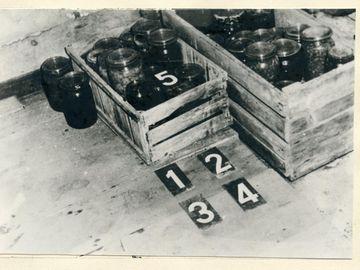 BStU, MfS, HA VII, Nr. 1626, Bl. 27  [Auf dem schwarzweißen Lichtbild sind zwei behelfsmäßige Holzvorratskästen in unterschiedlichen Größen zu sehen. Sie stehen an einer Wand, sind gefüllt mit Einmachgläsern, von denen auch zwei weitere noch daneben stehen. Vor der kürzeren Kiste sind vier schwarze Zahlentafeln (1 - 4) mit weißem Aufdruck. Die Ziffernkarte 5 liegt in der kleinen Aufbewahrungskiste.]  Detailaufnahme vom Keller Die Ziffern 1 - 4 verdeutlichen den Standort von 2 geleerten Erdbeergläsern, 1 geöffnetes Rotwurstglas, 1 Flasche Rotwein, aus der ein Teil des Inhaltes fehlt. Ziffer 5 zeigt die Stelle, an der vor dem Diebstahl die Flasche Rotwein und eine Flasche Sekt abgelegt waren. Ziffer 6 zeigte den Standort der 2 Erdbeergläser vor dem Diebstahl Ziffer 7 kennzeichnet den Standort einer halb entleerten Flasche Most.