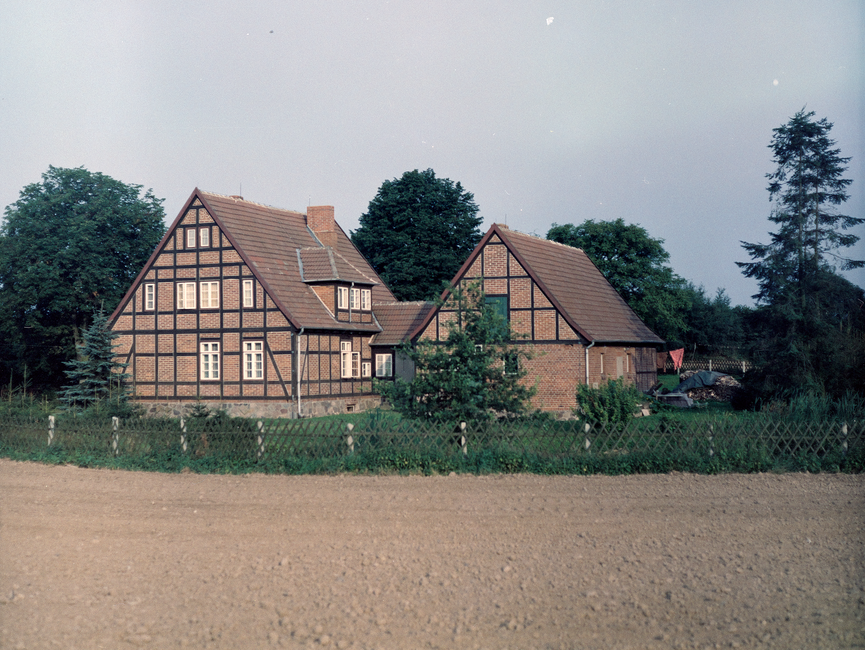 [Aufnahme zweier miteinander verbundener Fachwerkhäuser. Auf der Farbaufnahme lassen sich im Garten auch ein abgedeckter Holzhaufen swoei eine Wäscheleine erkennen.]