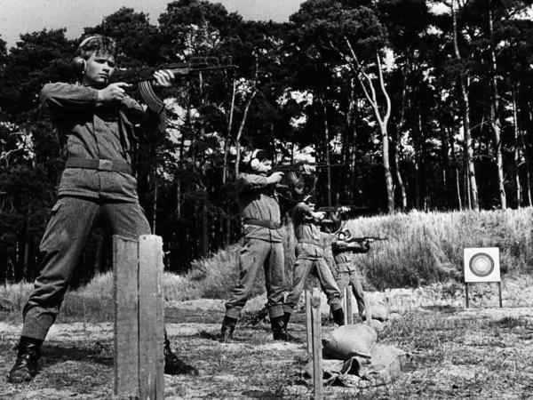 Das schwarzweiße Lichtbild zeigt im Halbprofil vier uniformierte Männer mit Gehörschutz beim Übungsschießen mit automatischen Waffen. Im mittleren Bildgrund steht eine Zielscheibe. Der Übungsplatz ist vor einem Kiefernwald gelegen.