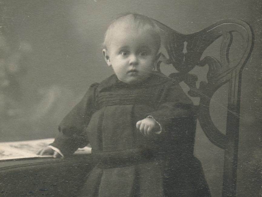 Es handelt sich bei dem schwarz-weißen Lichtbild um eine Ganzkörperportraitaufnahme von einem Kleinkind.  Das Kind steht auf einem gepolsterten Stuhl, hält sich am Tisch fest.