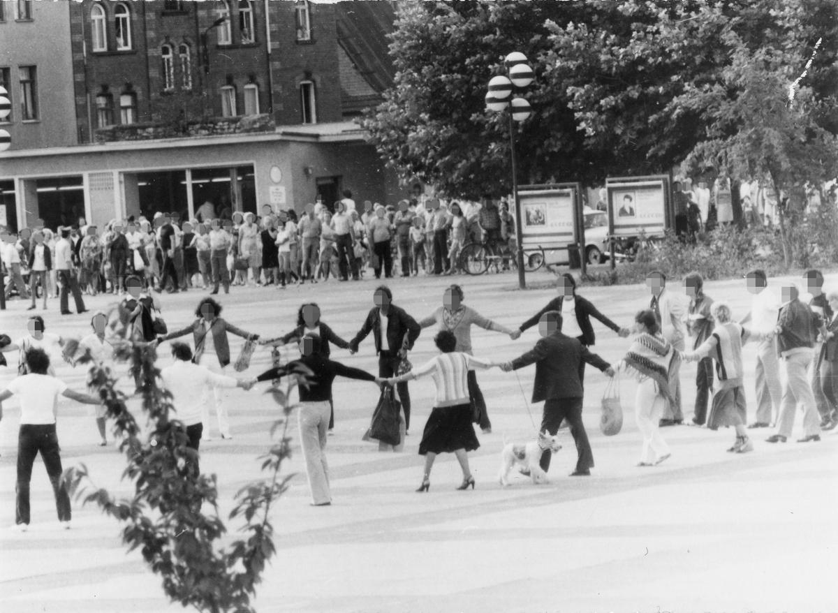 Eine Teilansicht des Demonstrantenkreises aus der Ferne fotografiert. Zu erkennen sind rund 20 Beteiligte. Im Hintergrund beobachten zahlreiche Zuschauer das Geschehen.