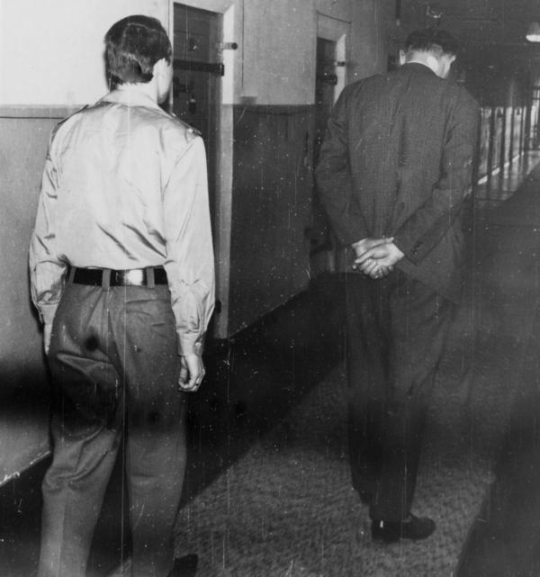 Ein Häftling geht durch den Zellengang. Ein Wärter begleitet ihn.