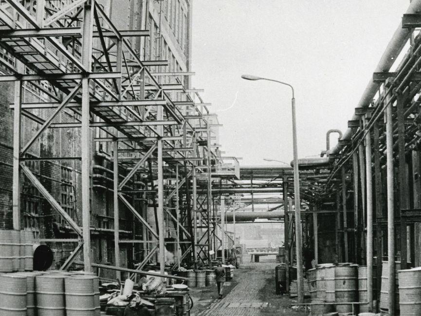 [Auf der schwarz-weiß Fotografie ist ein Teil eines Industriegebietes zu erkennen. Links ist ein mehrstöckiges Gebäude zu sehen, welches von einem Stahlgerüst umgeben ist. In der Mitte ist ein gepflasterter Weg zu erkennen, auf dessen linker Seite eine Person entlanggeht. Rechts am Weg entlang stehen Straßenlaternen. Auch ist auf dem Boden eine Mehrzahl von Tonnen zu sehen. Rechts neben dem Weg steht vermutlich eine Mauer, an der einige Rohre entlang führen. Im Hintergrund sind weitere Industriegebäude zu erkennen.]