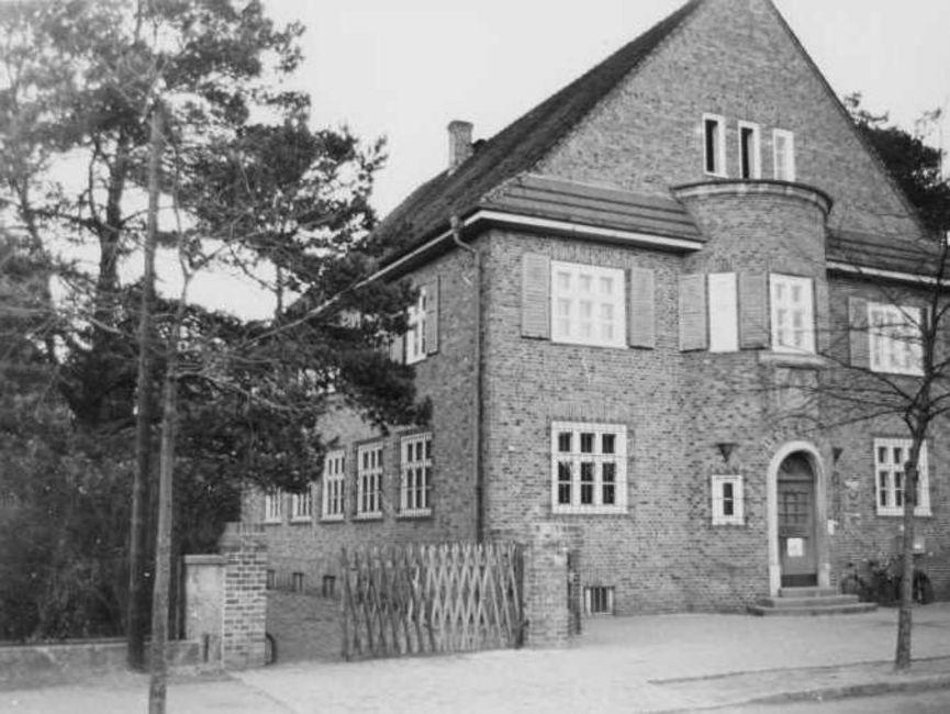 Das schwarz-weiße Lichtbild zeigt ein Backsteingebäude, zwei Etagen mit Spitzdach und Erker mit Eingangstür an der Schmalseite. Hinter einem Jägerzaun links neben dem Haus geht es in eine gepflasterte Auffahrt.