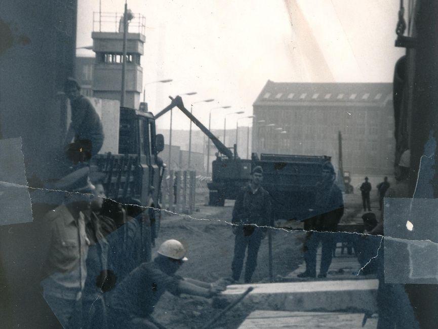 Das schwarz-weiße Lichtbild ist durch die Maschen eines Bauzauns aufgenommen worden und zeigt den Kontrollstreifen der Grenzanlagen, im Hintergrund ist ein Beobachtungsturm zu sehen. Das Foto dokumentiert Bauarbeiten an der Berliner Mauer. Es stehen mehrere uniformierte Männer um zwei Bauarbeiter herum, während ein Mauerstück mittels Kran abgesenkt wird. Das Foto war mittig zerrissen worden und ist nun manuell rekonstruiert.