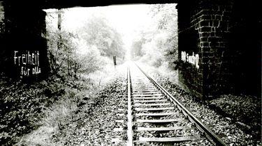 Auf dem schwarzweißen Lichtbild ist ein Gleisstrang abgebildet, der zwischen dichter Vegetation verläuft. Im Vordergrund zwei Brückenpfeiler, zwischen denen die Bahnstrecke verläuft, zu sehen. Der linke Brückenpfeiler wurde mit der Losung 'Freiheit für alle', der rechte Pfeiler mit 'DDR 5 nach 12' in weißer Farbe beschriftet.