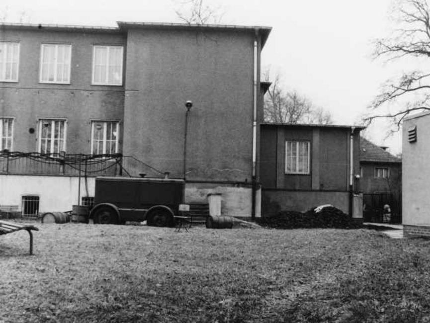 Das schwarz-weiße Lichtbild zeigt die Rückansicht des Haupthauses ab der linken Hälfte der kleinen Terrasse. Zu ihr führt eine Treppe mit Absatz, davor steht ein Notstromaggregat. Rechts davon liegt ein Kohlehaufen.