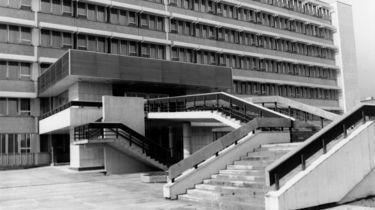 Das Schwarz-Weiß-Bild zeigt einen Teil des Stasi-Krankenhauses in Berlin-Buch. Zu sehen ist der Haupteingang mit einem kleinen Anbau, zu welchem eine Treppe hinaufführt.