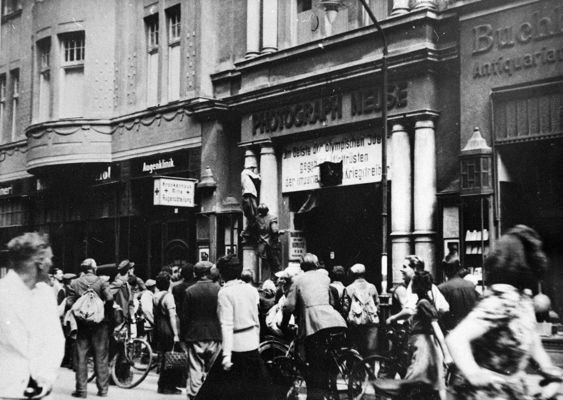 Demonstranten reißen in einer Ladenzeile in Görlitz SED-Plakate ab.