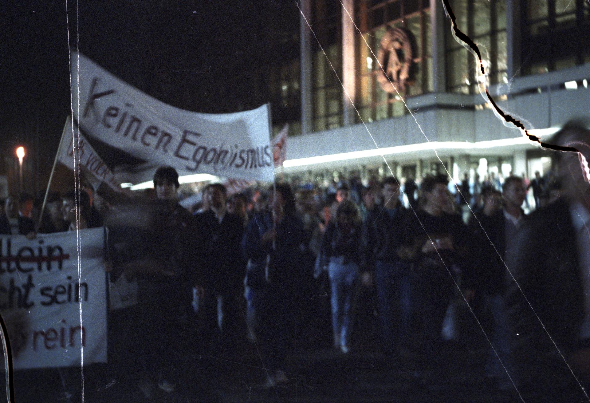 Ein Demonstrationszug vor dem Palast der Republik in Berlin-Mitte am Abend des 24. Oktober 1989 aus Protest gegen die Ernennung von Egon Krenz zum neuen Staatschef der DDR. Die Menschen marschieren am späten Abend, es ist dunkel und sie halten Kerzen in der Hand. Im Hintergrund ist der Palast der Republik zu sehen, das Staatswappen der DDR mit Hammer, Zirkel und Ährenkranz über dem Eingang hell erleuchtet. Die Demonstranten tragen Transparente, eines davon ist lesbar. 'Keinen Ego(n)ismus' steht darauf.