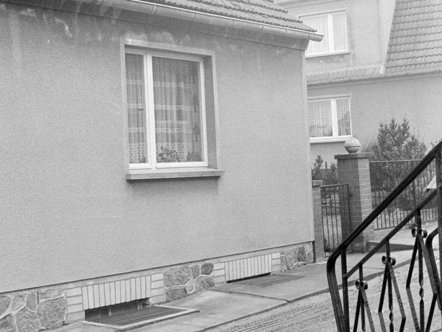 Das schwarz-weiße Lichtbild zeigt eine Hausecke eines Einfamilienhauses, der Haussockel ist mir Natursteinen gefliest. Zu sehen ist eines der Fenster sowie der anschließende Zaun des Nachbargrundstückes. In der rechten Bildecke sieht man das schmiedeeiserne Geländer einer Treppe.