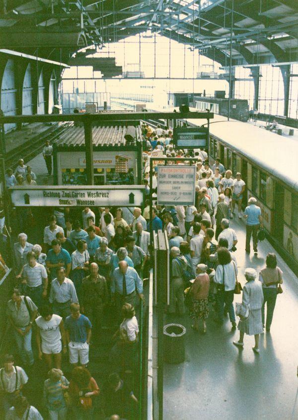 Menschen auf dem Bahnsteig. Am rechten Bildrand ist eine S-Bahn zu sehen.