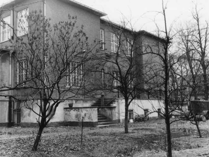 Die Rückseite des Haupthauses ist hinter mehreren kleinen kahlen Laubbäumen zu sehen. Zum Hintereingang führt jeweils eine Treppe mit einem Treppenabsatz, eine auf der linekn und eine auf der rechten Seite zu einer Art Terrasse. Der eigentliche Eingang ist nicht erkennbar. Es handelt sich um ein schwarz-weißes Lichtbild.