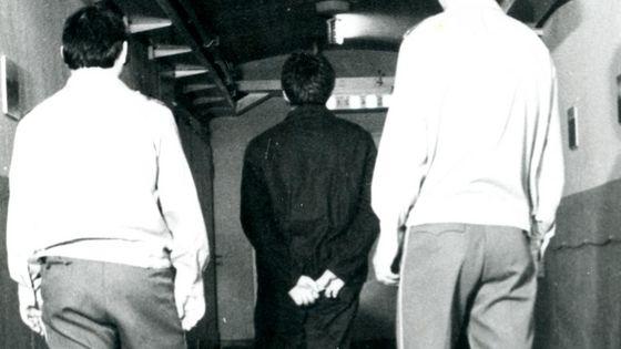Ein Häftling wird von zwei Aufsehern einen Gang entlang geführt.